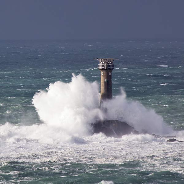 wave crashing over lighthouse in Cornwall